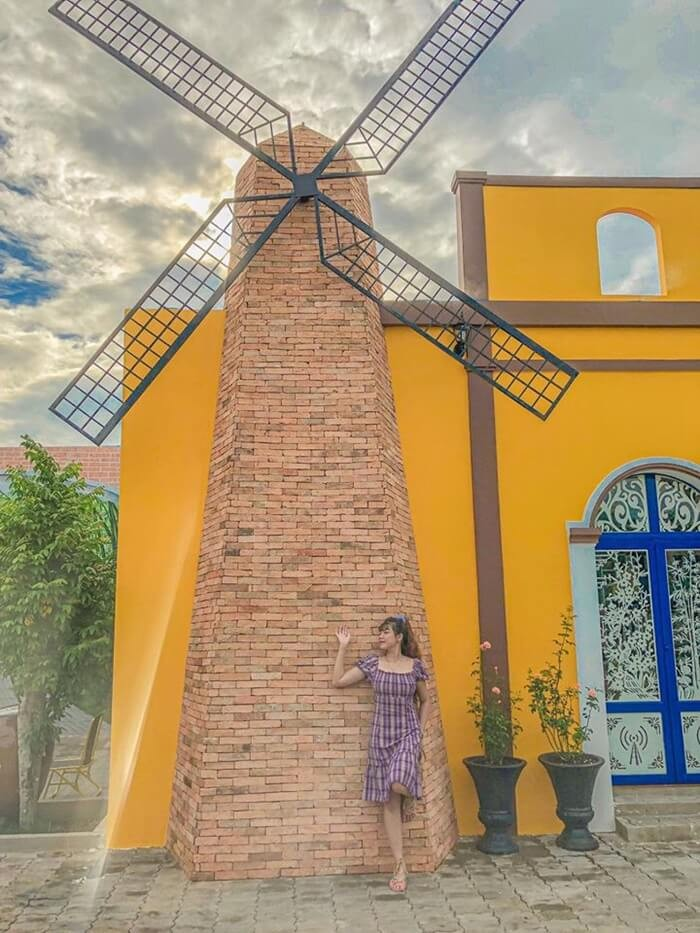 Purple house Can Tho - posing beside a windmill