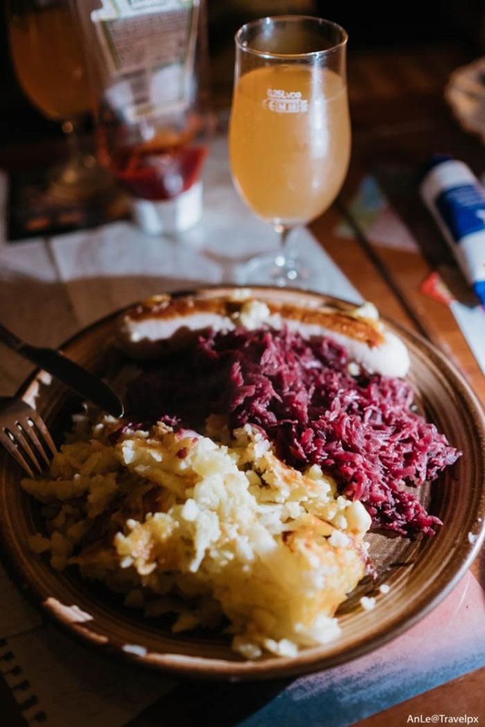 Bữa tối tại thị trấn cổ tích với một đĩa gồm khoai tây nghiền, xúc xích và cải muối của Thuỵ Sĩ, kèm apple juice, và một chiếc bánh táo.