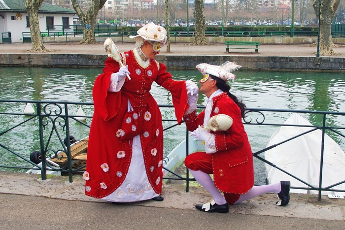 Two people wearing costumes by the canal de Vassé - Annecy Venetian Carnival